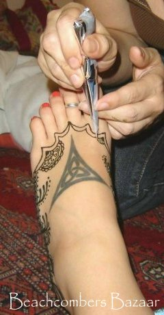 Jody using a traditional henna cone for mehndi tattoos.